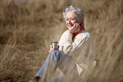 A senior woman sitting amongst the sand dunes, holding a hot drink : Stock Photo
