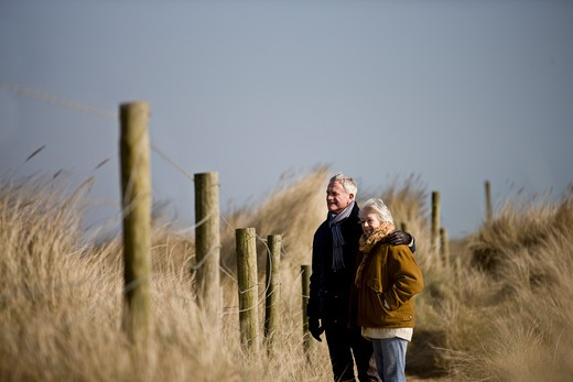 A senior couple walking, looking over a fence : Stock Photo