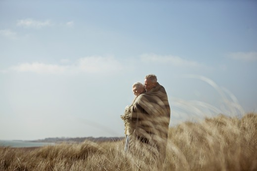 Stock Photo: 1804R-19935 A senior couple standing in sand dunes, wrapped in a blanket