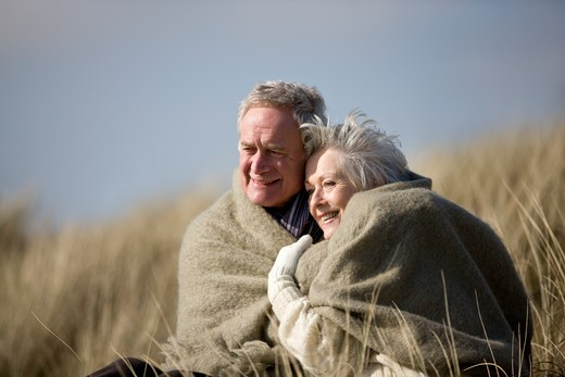 Stock Photo: 1804R-19937 A senior couple sitting amongst the sand dunes, wrapped in a blanket