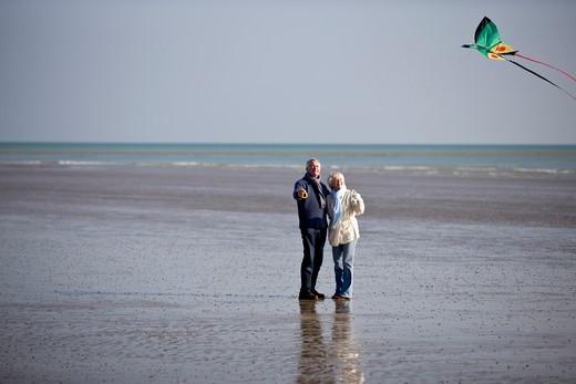 Stock Photo: 1804R-19959 A senior couple flying a kite on the beach