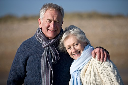 Stock Photo: 1804R-19971 Portrait of a senior couple standing on the beach