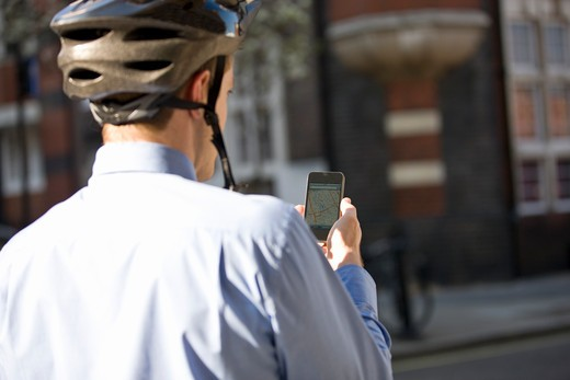 A businessman on his bicycle, looking at a map on his mobile phone : Stock Photo