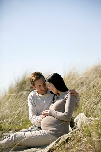 A pregnant woman and her partner sitting amongst the sand dunes : Stock Photo