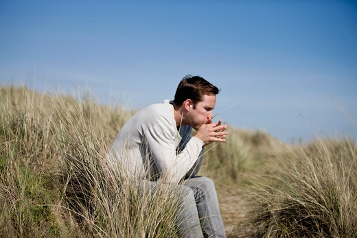 A young man sitting amongst the sand dunes, blowing on a blade of grass : Stock Photo