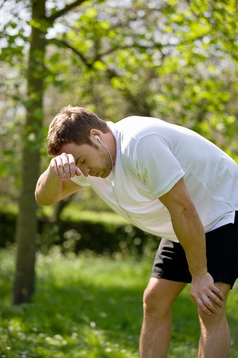 A young man taking a rest from running : Stock Photo