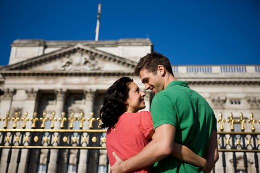 A young couple standing in front of Buckingham Palace : Stock Photo