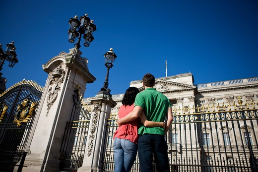 A young couple standing in front of Buckingham Palace, rear view : Stock Photo
