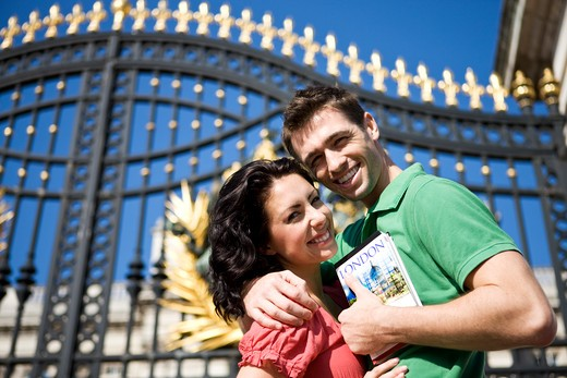 A young couple in front of Buckingham Palace, holding a guidebook : Stock Photo