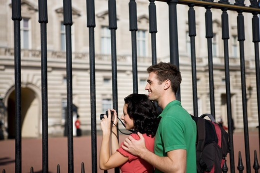 A young couple taking a picture of Buckingham Palace : Stock Photo