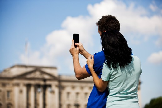 Stock Photo: 1804R-20395 A young couple taking a picture of Buckingham Palace