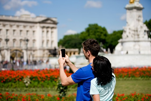 Stock Photo: 1804R-20397 A young couple taking a picture of Buckingham Palace
