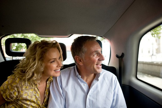Stock Photo: 1804R-20431 A middle-aged couple in a London taxi, admiring the view