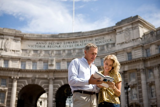 A middle-aged couple standing in front of Admiralty Arch, looking at a guidebook : Stock Photo