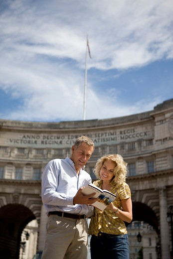 Stock Photo: 1804R-20433 A middle-aged couple standing in front of Admiralty Arch, looking at a guidebook