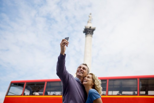 Stock Photo: 1804R-20446 A middle-aged couple taking a photograph of themselves in front of Nelson's column