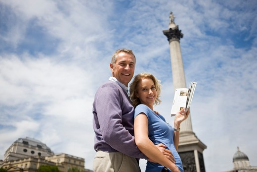 A middle-aged couple in front of Nelson's column, holding a guidebook : Stock Photo