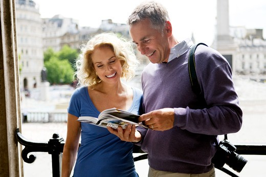 Stock Photo: 1804R-20456 A middle-aged couple standing by Trafalgar Square, looking at a guidebook