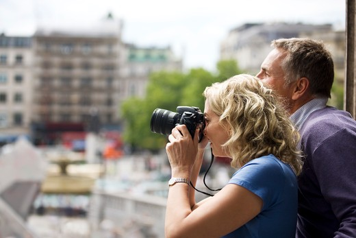 A middle-aged couple taking a photograph of Trafalgar square : Stock Photo
