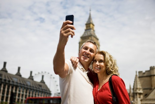 A middle-aged couple standing at Parliament Square, taking a photograph : Stock Photo