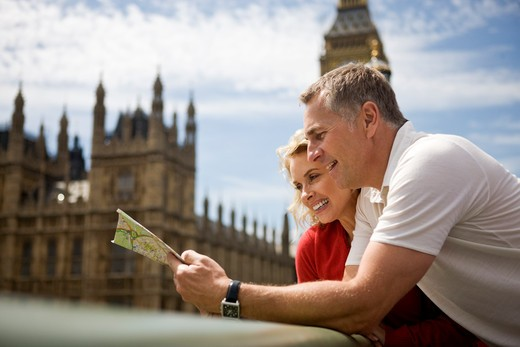 Stock Photo: 1804R-20474 A middle-aged couple standing near the Houses of Parliament, looking at a map