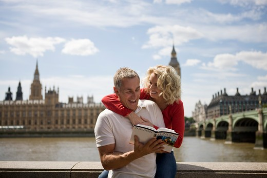 A middle-aged couple in front of the Houses of Parliament, looking at a guidebook : Stock Photo