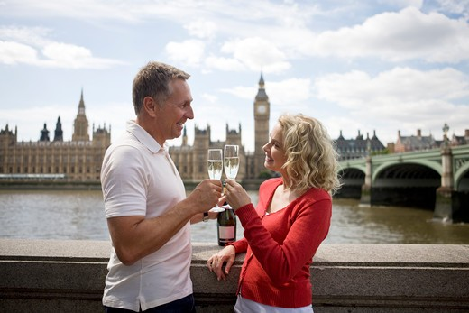 A middle-aged couple in front of the Houses of Parliament, toasting with champagne : Stock Photo