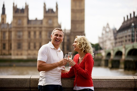 A middle-aged couple in front of the Houses of Parliament, drinking champagne : Stock Photo