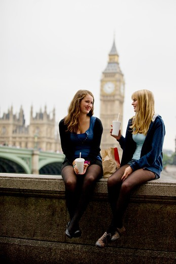 Two teenage girls sitting near Big Ben, having lunch : Stock Photo