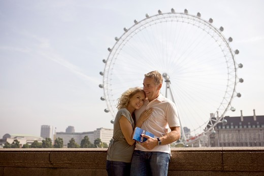 A middle-aged couple standing in front of the London Eye : Stock Photo