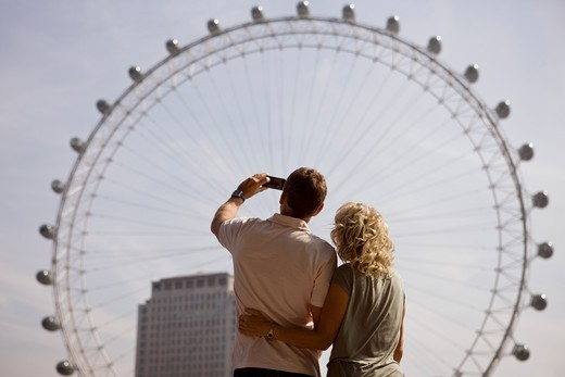 A middle-aged couple photographing the London Eye, rear view : Stock Photo