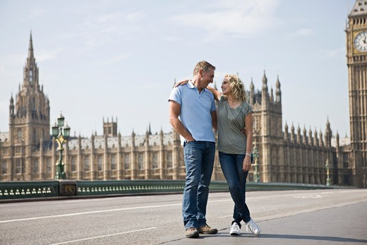 A middle-aged couple standing near the Houses of Parliament, embracing : Stock Photo