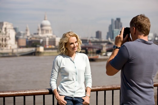 A middle-aged man taking a photograph of his partner next to the river Thames : Stock Photo