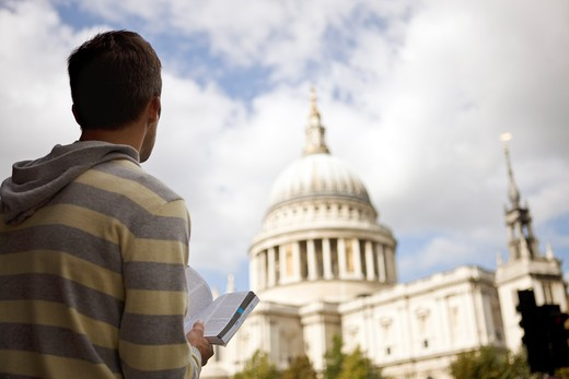 Stock Photo: 1804R-20600 A mid-adult man standing in front of St Paul's cathedral, looking at a guidebook