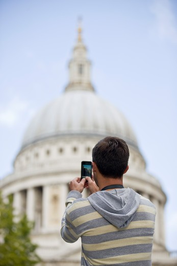 A mid-adult man taking a photograph of St Paul's cathedral : Stock Photo