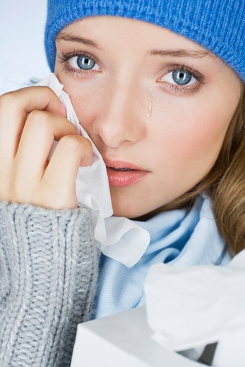 A young woman crying, wiping her tears away with a tissue, close-up : Stock Photo