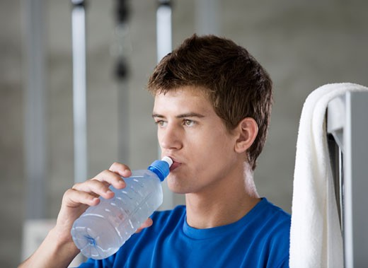 A young man drinking a bottle of water : Stock Photo