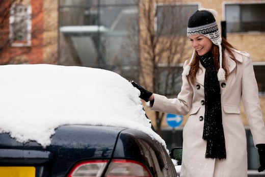 A young woman gathering snow off a car : Stock Photo