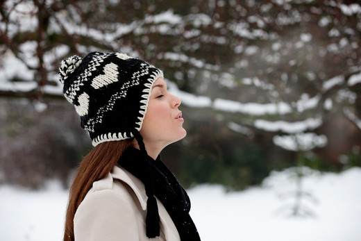 A young woman wearing a woolen hat, breathing into the cold air : Stock Photo