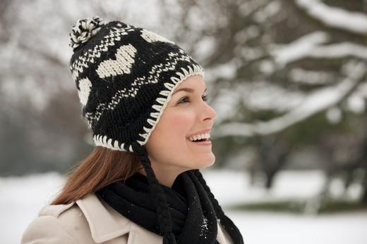 A young woman wearing a woolen hat, admiring the snow : Stock Photo