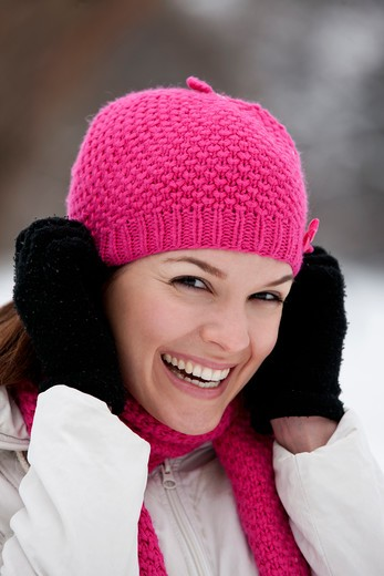 Stock Photo: 1804R-20876 A young woman putting on a pink woolen hat