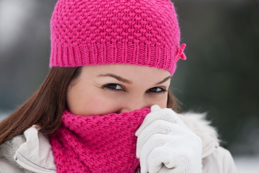 Stock Photo: 1804R-20878 A young woman wearing a pink hat and scarf, trying to keep warm