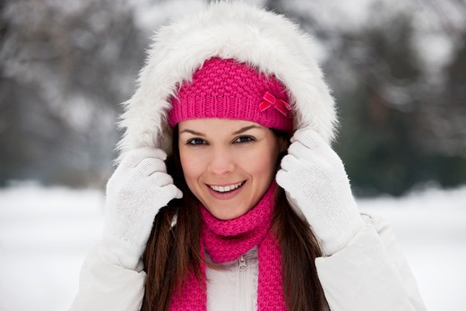 Stock Photo: 1804R-20880 A young woman putting up the hood of her coat, smiling
