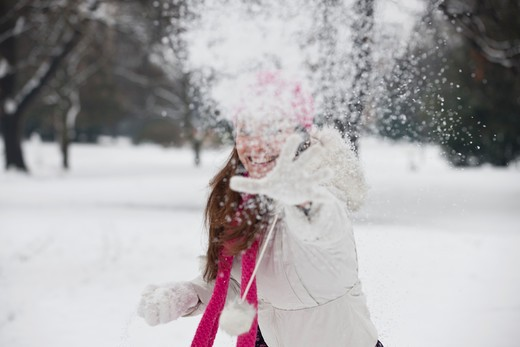 Stock Photo: 1804R-20891 A young woman throwing a snowball