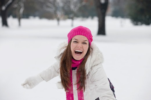 Stock Photo: 1804R-20892 A young woman throwing a snowball, laughing