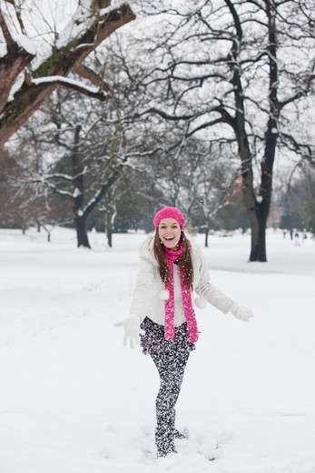 Stock Photo: 1804R-20893 A young woman throwing a snowball, smiling