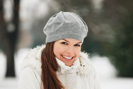 Stock Photo: 1804R-20894 A young woman wearing a grey woolen beret, smiling