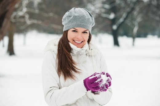 Stock Photo: 1804R-20895 A young woman wearing a grey woolen beret, holding a snowball