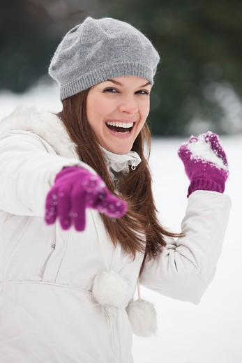 Stock Photo: 1804R-20901 A young woman throwing a snowball, laughing