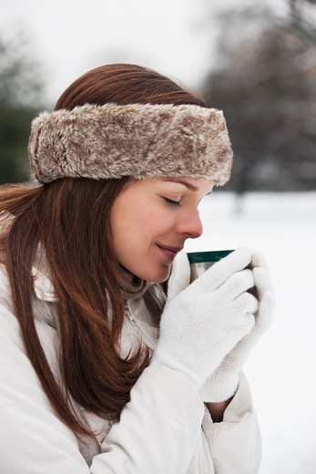 Stock Photo: 1804R-20911 A young woman wearing a fur headband holding a hot drink